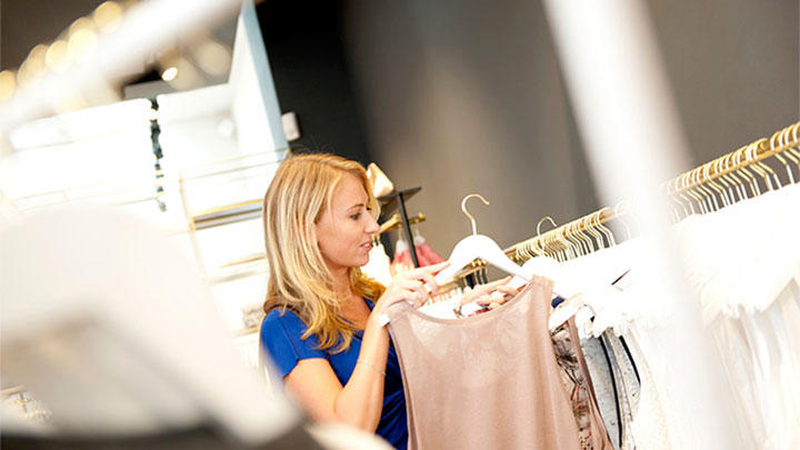 A woman shops at SuperTrash, a store with Philips retail lighting systems and innovative fitting room ligthing